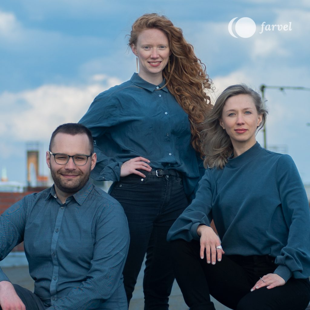 On the left you can see Founder Markus Traber, with dark brown hair and a beard. He is wearing dark framed glasses and a blue checked shirt. In the middle, you can see Founder Jennifer Beitel, standing with red curly hair. She is wearing long edgy brass earrings and a blue grey shirt. On the left, you can see Founder Lilli Berger, with blonde shoulder long straight hair. She is wearing a grey blue shirt.